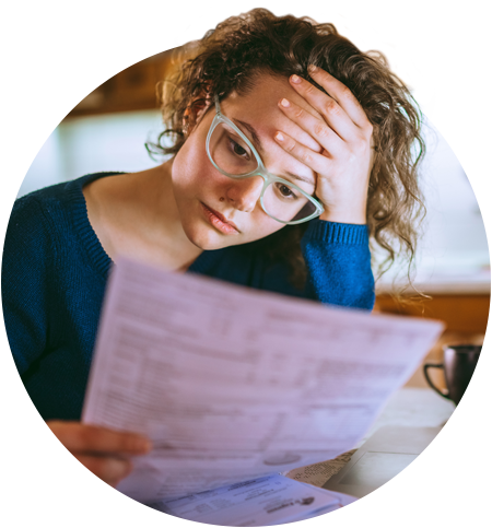 Photograph of a woman staring at paperwork and seeming frustrated