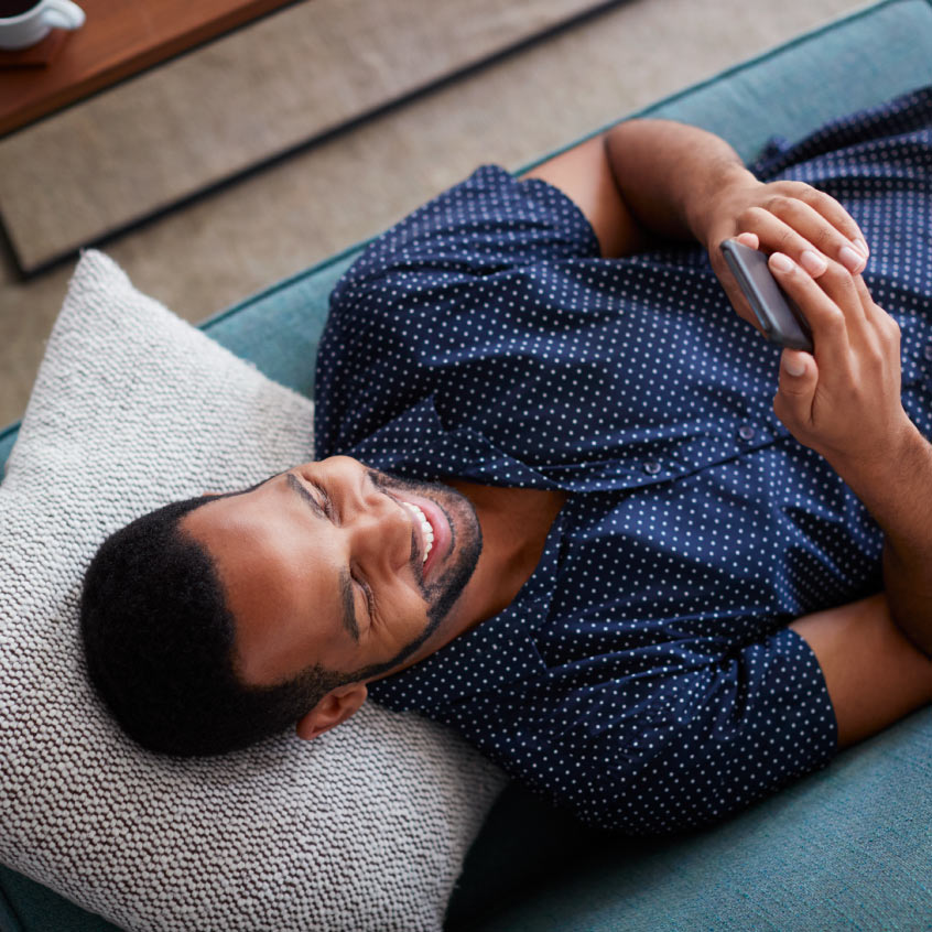 Man on laying down while looking at phone